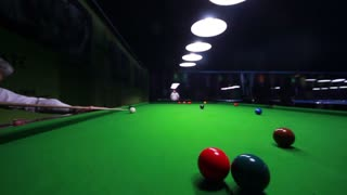 A handsome snooker player playing snooker in an entertainment center, he hits the black ball and it goes in...