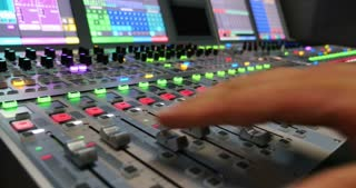 A left side shot of a colorful audio mixer and a man pulling up and down the knobs...