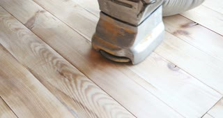 A low angle shot of a man sandering a parquet with a parquet sandering machine...