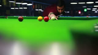 A low angle shot of a player playing snooker, he hits the red ball and it goes in...