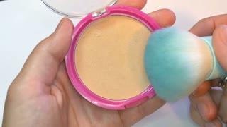 A make up artist taking some powder with a kabuki brush...