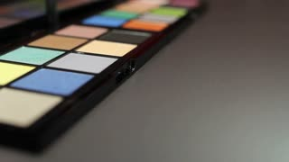 A make-up palette lying on a table and a make up artist sorting the brushes and prepares for giving a person a perfect look...
