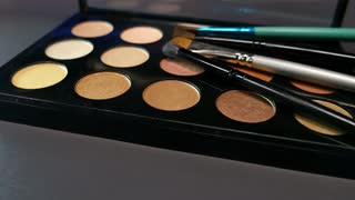 A make up palette lying on a table with some brushes lying on it, the shot is moving in a half circle