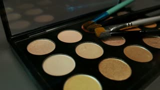 A make up palette lying on a table with some brushes lying on it, the shot is moving in a half circle....