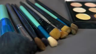 A make up palette with several brushes lying beside it, the shot is moving from one side to the other and vice versa...