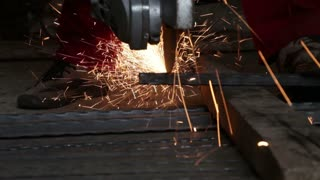 A man cutting pipes with a grinder... shot from a low angle...