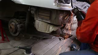 A man grindering a part of the car and preparing it for a general repair...