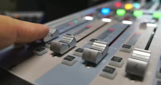 A man in a recording studio working on an audio mixer, he is pulling up the knobs, the shot is moving from left to right...