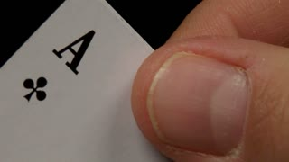 A man slowly shows his cards - he has got four aces
