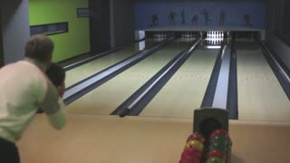 A man throwing a bowling ball in a bowling recreational center, he hits all the skittles...