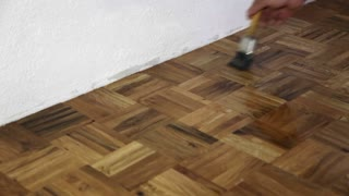 A man varnishing a parquet in a room...