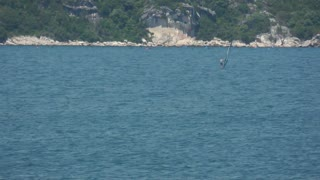 A man windsurfing on the sea surface...