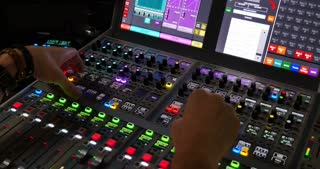 A man working in a studio on an audio mixer...