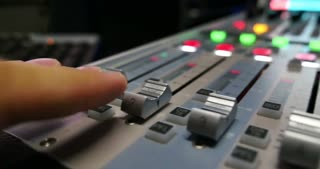 A mans hands pulling up the knobs of an audio mixer in a studio...