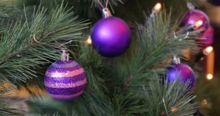 A moving footage of a decorated Christmas tree with purple balls on it...