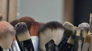 A moving shot of a lot of make-up brushes on a table...