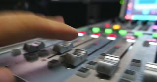 A moving shot of a man in a recording studio working on an audio mixer, the shot is moving from left to right...