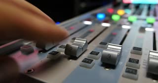 A moving shot of an audio mixer and a man pulling up the knobs on it, the shot is moving from the left to the right...