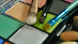 A moving shot showing a make up palette and some brushes lying next and on it...