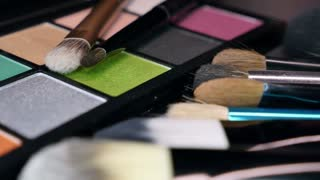 A moving shot showing a make up palette and some brushes next to it...