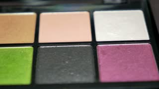 A moving shot showing a professional make-up palette, the shot is moving from right to left...