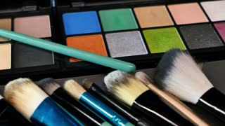 A moving shot showing a professional make-up palette with some brushes in front of it, the shot is moving from right to left...