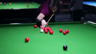 A moving shot showing a young man playing snooker, he hits and makes a point...