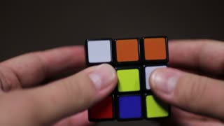 A person desperately trying to solve the Rubik´s cube, but it is not an easy task