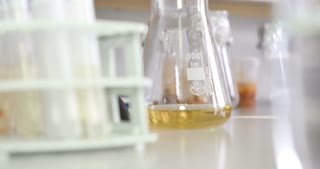 A person in a laboratory taking samples and puts them into test tubes
