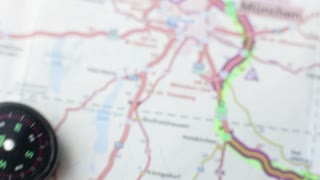 A person is holding a compass over a road map and trying to figure out where north is...