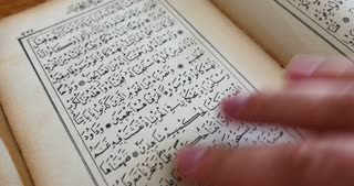 A person is leafing through an old Quran...