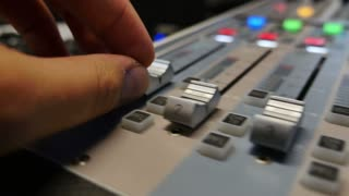 A person pulling up the knobs of an audio mixer in a studio...