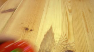 A person puts red, yellow and green paprika in the center of a wooden table and decorates it with a bunch of parsley...