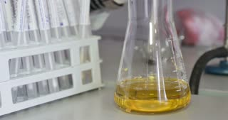 A person taking some samples from an erlenmeyers flask and puts them into test tubes