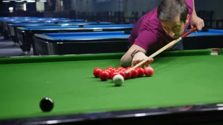 A player hits the black ball in a snooker game...