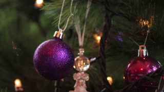A purple christmas ball hanging on a christmas tree, the shot is moving from the top to the bottom