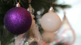 A purple christmas tree ball on a christmas tree with a white ball and some other christmas tree decorations in the background