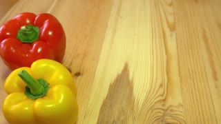 A red and yellow paprika standing next to each other on a whooden table while somebody pushes a green paprika next to them...