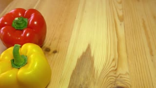 A red and yellow paprika standing next to each other on a wooden table while somebody places a green paprika next to them, the shot then goes out of focus...