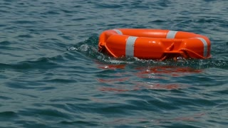 A red rescue buoy floating on the water surface