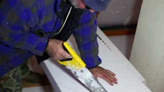 A repairman cutting the Styrofoam insulation with a saw...