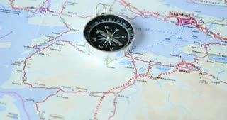 A road map showing Istanbul and Bursa with a compass on lying on the map...