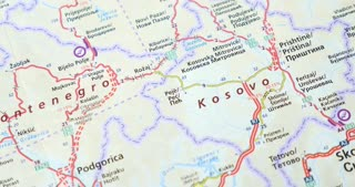 A road map showing Kosovo, Montenegro, Croatia and Bosnia, with a crazy compass at the bottom, the shot moves from right to left...