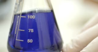 A scientist in a lab mixes an Erlenemeyer flask with some blue content in it