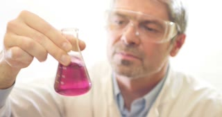 A scientist in a lab mixing a red content in an erlenmeyers flask looks into camera and smiles