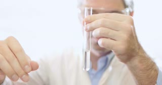 A scientist in a lab putting some chemicals into a test tube due to test the hardness of the water