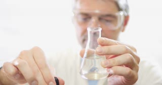 A scientist in a lab putting some chemicals into an erlenmeyers flask due to test the hardness of the water - the water is soft and the content  becomes blue
