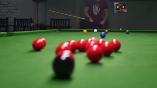 A shot behind the snooker balls and a young man tries to make the perfect shot...
