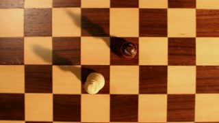 A shot from above a chess board and two kings standing on it, the white king overthrows the black...