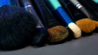 A shot moving in a half circle showing a make up palette with a lot of brushes next to it...